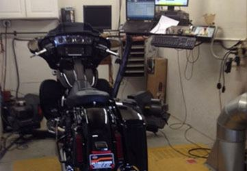 A black motorcycle near the Dyno machine.